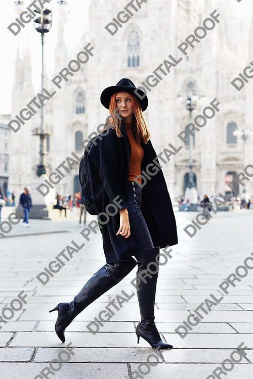 Fashion model walking by the Duomo of Milan looking back wearing a hat and a dark coat and a backpack in a October morning