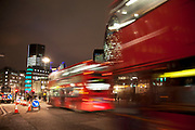 Night time scene in the City of London. Red buses pass in a blur as rush hour begins and the commute home starts.