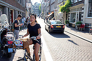 In Amsterdam rijdt een toerist op een huurfiets door de binnenstad.<br /> <br /> In Amsterdam a tourist is riding a rental bike downtown.