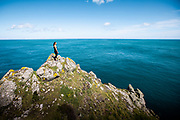 Woman out for a run on the north coast cliff paths stopping on top of the rocks to take in the view of the sea and coastline on a Spring day in Jersey, Channel Islands
