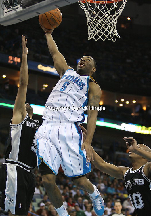 Mar 01, 2010; New Orleans, LA, USA; New Orleans Hornets guard Marcus Thornton (5) attempts a shot between San Antonio Spurs guard Tony Parker (9) and guard Keith Bogans (10) during the second half at the New Orleans Arena. The Spurs defeated the Hornets 106-92. Mandatory Credit: Derick E. Hingle-US PRESSWIRE
