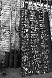 Price list chalked on blackboard outside shop shows prices of many brands of cigarettes in a Beijing hutong