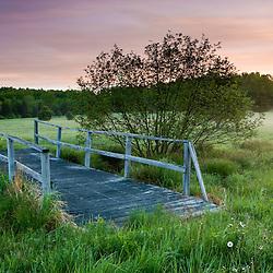 A footbridge spans a small stream in a field at Highland Farm in York, Maine.