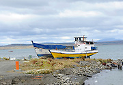 Wooden fishing boats pulled up on the beach.Puerto Natales, Chile. 17Feb13