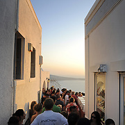 Crowds of people on narrow street of Oia town Santorini watch the sunset