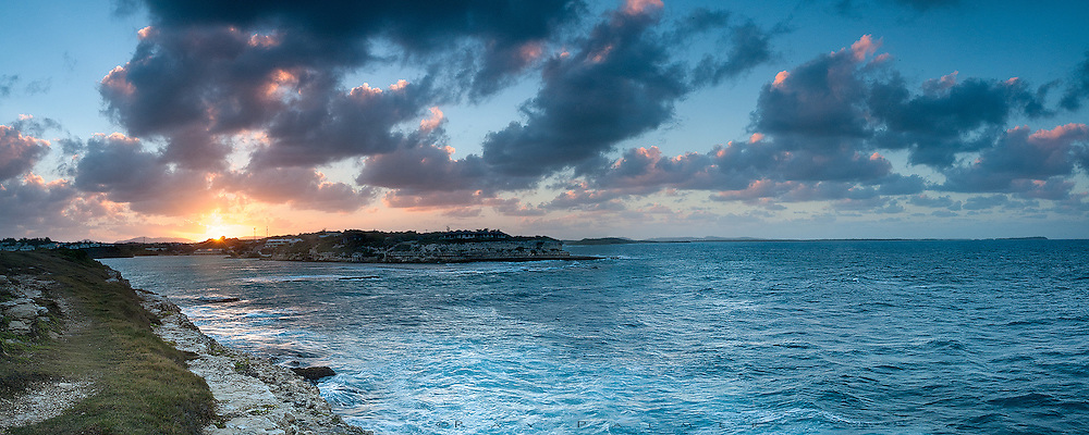 Most sundowns and sunrises, I would take off alone and haunt the headland of Indian Town Point, home of the Devil's Bridge and one of Antigua's national parks.  The big skies out here were always full of approaching  clouds from the west, while off shore to the east they hovered forever as though afraid to move on.  The ocean raged against the point of the headland behind me, but where I stood here on a cliff edge above the northern side, the waves seemed to  race past on their way into the bay beyond, churning and angry that they didn't hit the point.  The legendary winds out here threatened to push me with them.  This evening the sun only gave up color at the end, briefly tenderizing the sky before quickly winking out below the horizon.  This is an 8 image panorama, stitched in Photoshop.