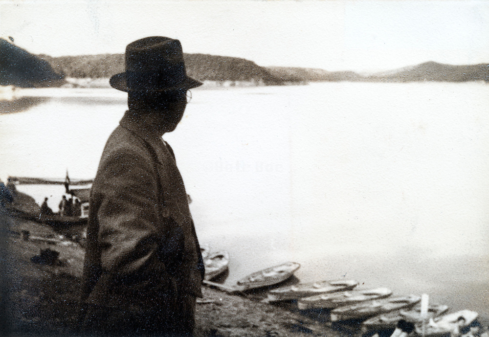 man looking over a big lake or sea with mountains in the distance Japan ca 1950s