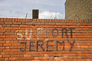 'Support Jeremy' (Jeremy Corbyn, - the left-wing Labour leader elected in September 2015) writing on a Nunhead, south London brick wall. Roughly painted on to the Victorian bick wall is the message dated to the Labour leadership campaign, eventually controversially won by Corbyn. Above the writing we see barbed wire - as if the message of a dystopian, Orwellian political landscape.