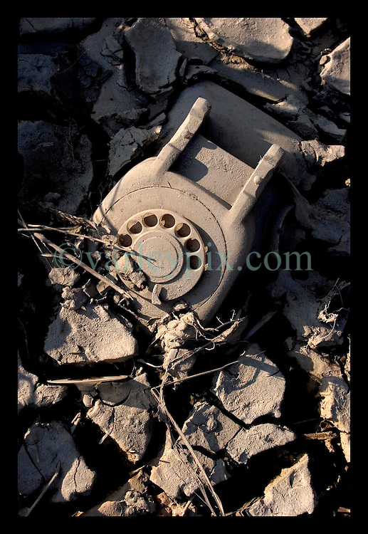 30th Sept, 2005. Hurricane Katrina aftermath, New Orleans, Louisiana. Lower 9th ward. The remnants of the lives of ordinary folks, now covered in mud as the flood waters remain. a telephone lies stuck in the mud.