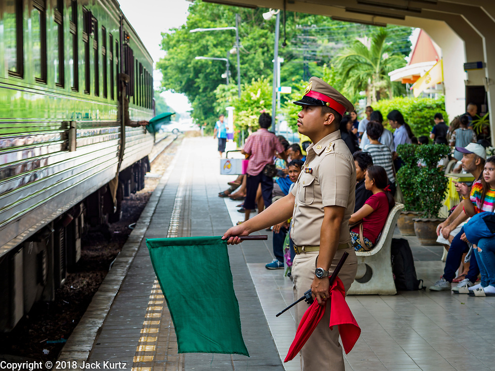 10 JULY 2018 - NAKHON PATHOM, THAILAND:  A station agent waves a train out of the station in Nakhon Pathom. Nakhon Pathom is about 35 miles west of Bangkok. It is one of the oldest cities in Thailand, archeological evidence suggests there was a settlement on the site of present Nakhon Pathom in the 6th century CE, centuries before the Siamese empires existed. The city is widely considered the first Buddhist community in Thailand and the nearly 400 foot tall Phra Pathom Chedi is considered the first Buddhist temple in Thailand.    PHOTO BY JACK KURTZ