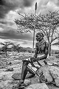 A portrait of a Samburu warrior sitting on a rock, black and white,,Samburu, Kenya, Africa