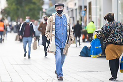 © Licensed to London News Pictures. 13/10/2020. Liverpool, UK. Member of the public wears a face mask in Liverpool, which is due to enter Tier 3 lockdown on Wednesday. The lockdown will see the closure of pubs, bars, bookmakers, gyms and casinos as well as a ban on overnight stays outside of the home. Photo credit: Kerry Elsworth/LNP