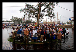 30th August, 2005. Aftermath of Hurricane Katrina, New Orleans, Louisiana. national guardsmen encounter hundreds of refugees from the lower 9th ward awaiting transportation to the refugee camp that is the Superdome. The thousands of people gathered on the only high ground they could find at the St Claud avenue bridge.