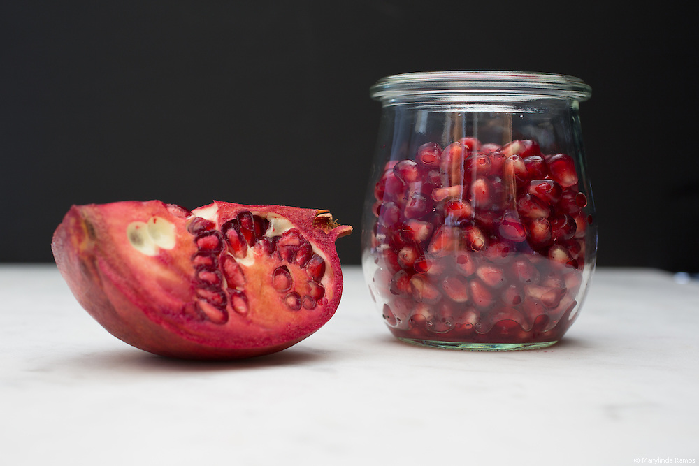 Front view of a glass container of pomegranate arils (seeds).  A quarter of a pomegranate sits to the left.