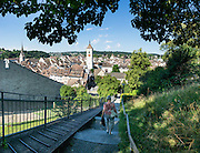 The Munothaldenweg / Munot pathway descends from the Munot's rose garden to the Old Town of Schaffhausen, in Switzerland, Europe. At center is the steeple of St. Johann Church. At left is the steeple of Münster zu Allerheiligen / All Saints' Minster, built in 1103 (replacing the first church built in 1049). This image was stitched from multiple overlapping photos.