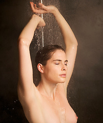 Close up of a woman showering with arms over head