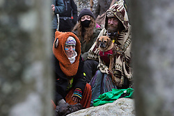 Over one hundred people, including local residents, climate and land justice activists and pagans, take part in a Mass Trespass at Stonehenge on 5th December 2020 in Salisbury, United Kingdom. The trespass was organised in protest against the approval by Transport Secretary Grant Shapps of a £1.7bn project for a two-mile tunnel beneath the World Heritage Site and a further eight miles of dual carriageway for the A303, as well as the government's £27bn Road Investment Strategy 2 (RIS2).
