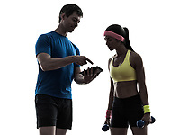 one woman exercising fitness workout with man coach using digital tablet in silhouette on white background