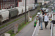 """Central american migrants look into the train wagons from a pedestrian bridge in Tultitlán on on August 3rd, 2012.  Tultitlán local authorithies ordered to dismantle the temporary shelter that was placed under a bridge in Tultitlán after shelter  """"San Juan Diego Cuauhtlatoatzin"""" in Lecheria, was closed on July 9th, 2012. (Photo: Prometeo Lucero)"""