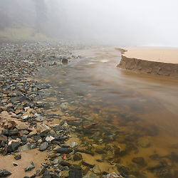 A tidal creek cuts a path through the sand on Sand Beach in Acadia National Park.