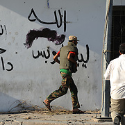 Rebel fighters run to cover during combats against troops loyalist Muammar Gaddafi's regime in central Zawiyah.