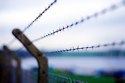 Barbed wire strung between concrete posts on top of a mesh security fence, England, UK.