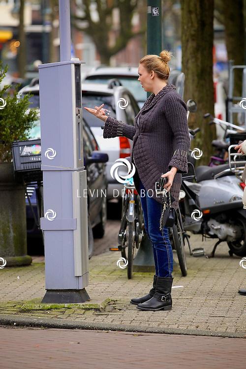 AMSTERDAM - Myrthe Mylius hier op de foto zwanger is aan het stoeien met de parkeermeter. FOTO LEVIN DEN BOER - PERSFOTO.NU