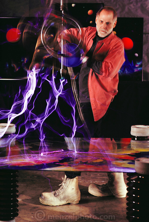 """Dave Archer, Novato, California-based artist, in his studio creating space art on glass using the 7-foot """"lightning brush"""" of his 1.5-million-volt Tesla coil. Paint is applied and then zapped with the point of a """"lightning brush"""" for nebulae effect; then he hand paints planets and stars. Methyl alcohol makes paint burst into flames and vaporize on the glass. MODEL RELEASED (1992)"""