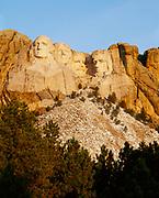 Morning light illuminating the faces of George Washington, Thomas Jefferson, Theodore Roosevelt and Abraham Lincoln, Mount Rushmore National Memorial, South Dakota.