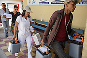 Health workers carrying cold boxes arrive back at the health center after carrying out house-to-house vaccination in San Esteban, Honduras on Thursday April 25, 2013.