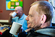 Men talk and get warm inside the centre of Slough Homeless our concern (SHOC) A local homeless charity helping the homeless and vulnerable in Slough. Berkshire, UK.