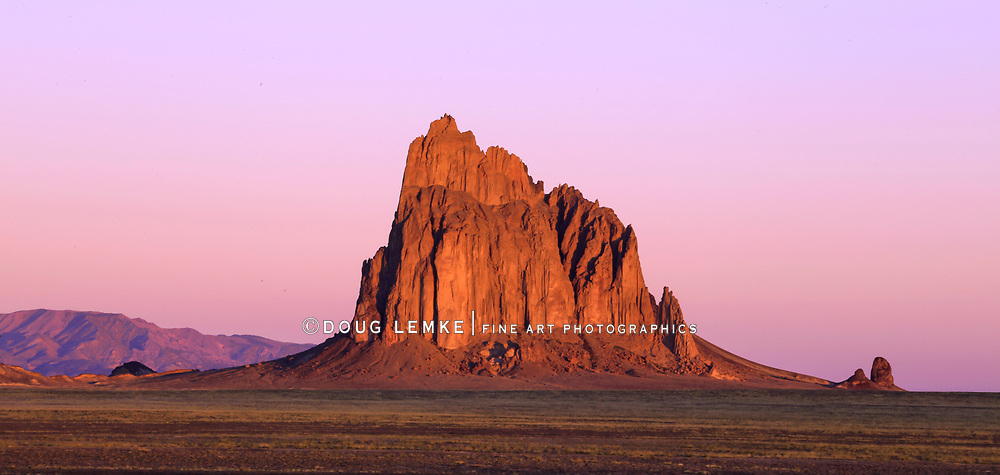 Ship Rock glows bright red with the first rays of the sun in early morning,, New Mexico; USA