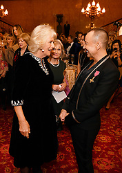 The Duchess of Cornwall meets Julien Macdonald before his fashion show at a reception at Lancaster House in London, which is supporting the National Osteoporosis Society charity.