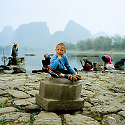 Liu Tong, 5 is pictured on the banks of the River Li, in Fulli Town Village, Guangxi province, where he lives with his grandmother, Wang Li Hua, 82 and his mother, Zhao Juan, 35. His grandmother still works on the family farm and his mother works in the tourist industry.The day we took this picture was the first day his grand mother had been on a boat and Tong's first ever day in the town of Yangshuo across the river from where they live. ..Its over thirty years (1978) since the Mao's Chinese government brought in the One Child Policy in a bid to control the world's biggest, growing population. It has been successful, in controlling growth, but has led to other problems. E.G. a gender in-balance with a projected 30 million to many boys babies; Labour shortages and a lack of care for the elderly.