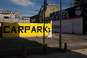 Woman walks past a large yellow car park sign on street in East London.