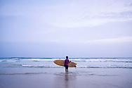 Mirissa beach, Sri Lanka. A child is entering the water to surf