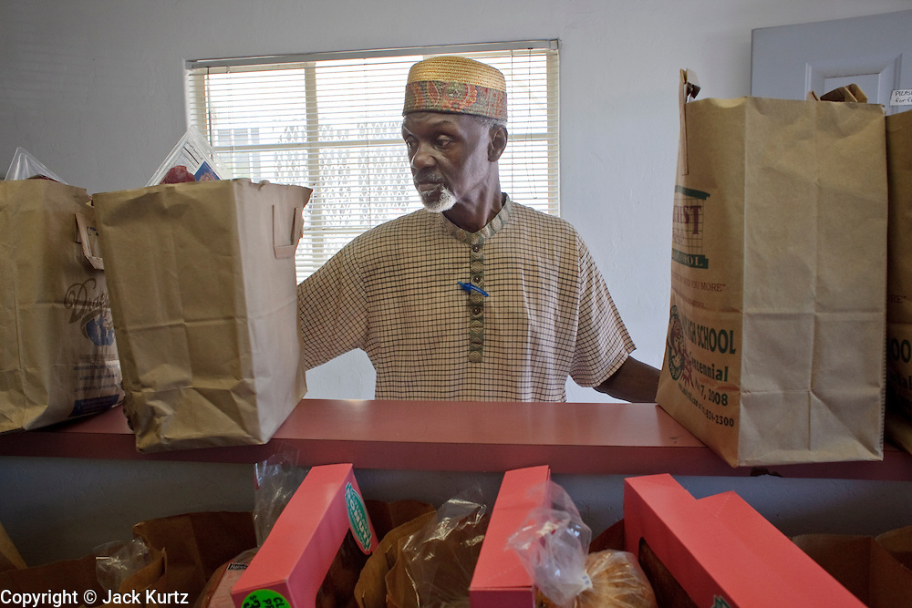 22 JUNE 2009 - PHOENIX, AZ: Habibulllah Saleem, husband of Cultural Cup food bank founder Zarinah Awad, sorts bags of food before distributing them at the food bank. The Cultural Cup has become a sort of community center. It started as a food bank and has since grown to include a clothing bank and free walk in clinic. The walk in clinic at the Cultural Cup Food Bank started two years ago when Cultural Cup founder Zarinah Awad wanted to expand the food bank's outreach and provide basic medical care for the people who use the food bank. The clinic sees, on average, 7 - 11 patients a week. Awad said that as the economy has worsened since the clinic opened and demand has steadily increased. She attributes the growth to people losing their jobs and health insurance. The clinic is staffed by volunteers both in the office and medical staff. Adults are seen every Saturday. Children are seen one Saturday a month, when a pediatrician comes in. Awad, a Moslem, said the food bank and clinic are rooted in the Moslem tradition of Zakat or Alms Giving, the giving of a small percentage of one's income to charity which is one of the Five Pillars of Islam.   PHOTO BY JACK KURTZ