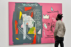 """© Licensed to London News Pictures. 23/06/2017. London, UK. Artist Bradley Theodore views """"New Flame"""", 1985, a collaborative work by Andy Warhol and Jean-Michael Basquiat (estimate GBP1.7-2.2m) at the preview of Sotheby's Contemporary Art Sale in New Bond Street.  The auction, which is dominated by Pop art, takes place on 28 June. Photo credit : Stephen Chung/LNP"""