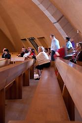 """È stata inaugurata il 1° luglio 2004, la nuova Chiesa di San Pio da Pietrelcina progettata dall'architetto Renzo Piano. Esattamente 45 anni prima, nel 1959,  veniva inaugurata la chiesa """"grande"""" di Santa Maria delle Grazie. .Sorta a fianco del santuario e convento in cui visse il frate, ha la forma di una conchiglia e la sua pianta ricorda quella della spriale archimedea. Enormi archi parto dal perimetro esterno e terminano nel fulcro della """"conchiglia"""" dove è posto l'altare. Possenti staffe d'acciaio, ancorate agli archi, sorreggono la volta che ricoperta di rame preossidato espone alla vista un intenso un colore verde-rame.   .Con i suoi 6000 mq, è la seconda chiesa più grande in Italia per dimensioni, dopo il Duomo di Milano. Può ospitare oltre 7000 persone e per la sua realizzazione sono state impiegati 30.000 metri cubi di calcestruzzo, 1.320 blocchi in pietra di Apricena, 70.000 metri cubi di scavo in roccia, 60.000 chili di acciaio, 500 mq di vetro, 19.500 mq di rame preossidato. Ogni anno è meta di oltre sei milioni di pellegrini..Nella foto alcuni fedeli raccolti in preghiera."""