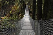 Crossing the suspension bridge at Cascade Falls Regional Park near Mission, British Columbia, Canada