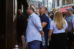 With all the pubs full, fans have to peer through the windows to see the action in Wardour Street, Soho. London, July 11 2018.