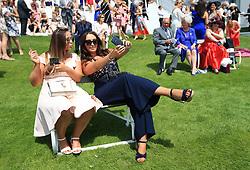 Female racegoers take a selfie on Ladies Day during the 2017 Investec Epsom Derby Festival at Epsom Racecourse, Epsom.