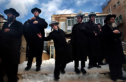 JERUSALEM, ISRAEL - FEBRUARY 27:An Orthodox Jewish boy slips on the ice as he watches  the funeral for a rabbi in Jerusalem, Israel February 27, 2003.  Thousands of people gathered to take part in the funeral procession.  (Ami Vitale/Getty Images).