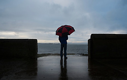 © Licensed to London News Pictures. 19/01/2014<br /> <br /> Teesside, England<br /> <br /> Martin Smith stands looking out over the mouth of the Tees as heavy rain falls.<br /> <br /> Photo credit : Ian Forsyth/LNP