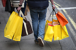 © Licensed to London News Pictures. 19/12/2015. London, UK. A shopper carries his purchases in Oxford Street on the last Saturday before Christmas. Photo credit: Peter Macdiarmid/LNP