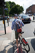 Man riding a Santander bike hire cycle in London, England, United Kingdom. The scheme, sponsored by Santander is intended to get Londoners cycling. As part of a major initiative. These free for the first half hour bikes are then charged for how long you use them. Take a cycle, ride it where you like, then return it, ready for the next person. Available 24 hours a day, all year round. Its self-service and theres no booking.