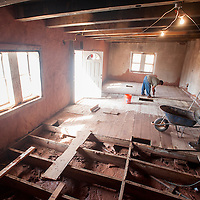 091813        Brian Leddy<br /> A man pulls up the floor boards at a home in Zuni Wednesday. Recent heavy rains brought water into the home and was one of many damaged in the area.