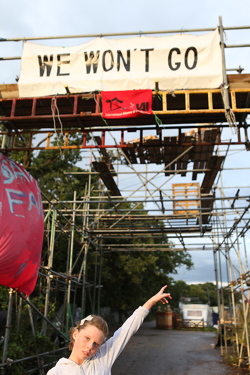 """Irish Traveller girl showing the """"We won't go"""" sign. Dale Farm in Essex, the UK largest Travellers' site. To support the Irish Travellers who own the land but never got planning permission and were about to be evicted by Basildon Council, some activists set up a Camp, called Camp Constant (after the name of the bailiffs' company, Constant & Co). <br /> Irish Traveller grumpy boy outside his family's caravan in Dale Farm. The largest Traveller community in the UK, Dale Farm was under threat of bulldozing. Ninety families were facing the largest eviction of its kind in recent memory, a nightmare which forced its residents to camp again on roadsides and car-parks as the site was finally and violently evicted in October 2011."""