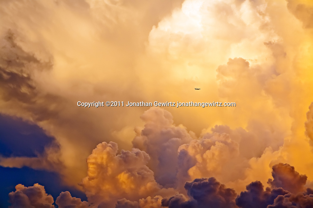 A distant airplane flies past towering thunderstorm clouds. WATERMARKS WILL NOT APPEAR ON PRINTS OR LICENSED IMAGES.