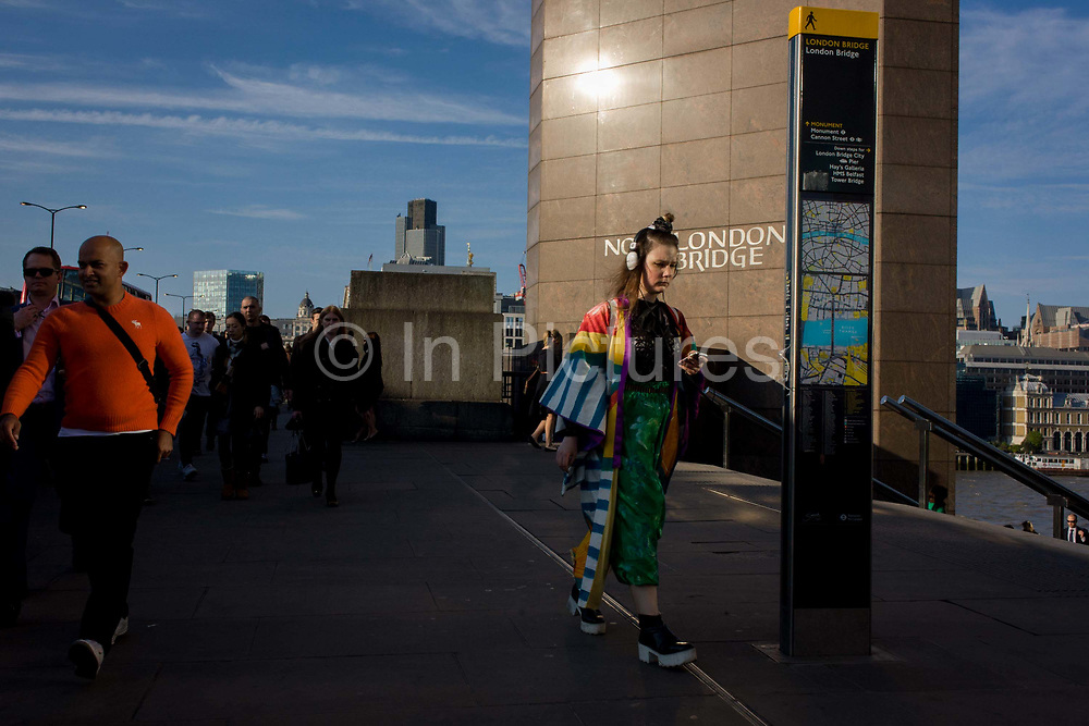 Londoners cross southbound over London Bridge during the evening rush hour. A young woman wears bright, stylish, clothing, a personal fashion statement on this trendy lady. Passing a city map pillar and the wall of <br /> some Eighties architecture at Number One, London Bridge. Commuters stride alongside others walking out of the City of London. There has been a crossing over the Thames here since the Romans first forded the river in the early 1st Century with subsequent medieval and Victorian stone bridges becoming an important thoroughfare from the City on the north bank, to Southwark on the south where transport hubs such as the mainline station gets commuters to the suburbs and satellite towns.
